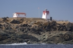 On the rocky shoreline, two buildings stand on Fishing Point Park in Newfoundland, Canada which are known as the St. Anthony Lighthouse and the light keeper's quarters.
