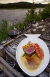 A delicious dinner of beef and lobster tail accompanied by a glass of wine prepared by the gourmet chef at the Rifflin'Hitch Lodge in Southern Labrador, Canada.