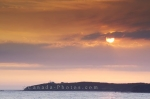 Beautiful sunset above Lobster Cove Lighthouse photographed from Rocky Harbour in Gros Morne National Park.