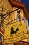 Along the Lighthouse Route in the town of Lunenburg, Nova Scotia, a bright yellow/orange colored sign hangs outside the Trattoria Della Nonna Restaurant and Pizzeria.