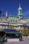 In the background the historic building of the Montreal City Hall in Quebec, Canada adorns the skyline while a vendor sets up his market stall in the foreground.