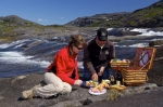 The stunning scenery of the Mealy Mountains and a waterfall in Southern Labrador, Canada creates the ideal surroundings to enjoy a picnic lunch.