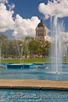 A variety of water shoots from each fountain located in Memorial Park in the City of Winnipeg, Manitoba with the Legislative Building displaying a beautiful backdrop.