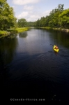 A kayaker enjoys the peacefulness along the Mersey River in Kejimkujik National Park in Nova Scotia, Canada.