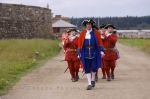 Down the street of the Quay at the Fortress of Louisbourg in Cape Breton, Nova Scotia, a parade of the military band is seen before the cannon gun firing.
