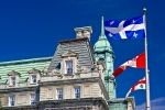 A variety of flags on the flag pole outside the historic building which houses the Montreal City Hall in Quebec, Canada.