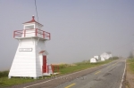 The Port George Lighthouse in Nova Scotia, Canada is located along the side of the main town road as the fog bank blankets the Port George Harbour in the Bay of Fundy.
