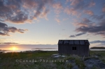 An old rustic shed sits along the banks of the peninsula in the outdoor beauty of the sunset in L'Anse aux Meadows in Newfoundland Labrador.