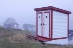 A red and white wooden outhouse on the grounds of the Church of St James the Apostle on Battle Island in Southern Labrador, Canada.