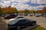 Cars and people fill the parking lot at the West Gate of Algonquin Provincial Park in Ontario, Canada on a sunny afternoon.