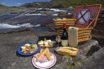 A picnic basket full of an assortment of food and drink sits atop a rock beside a waterfall in the Mealy Mountains in Southern Labrador, Canada.