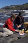 The scenery of a waterfall adorns the landscape of the Mealy Mountains in Southern Labrador while a couple enjoys their picnic lunch.