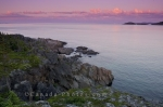 Along the Ocean View Trail in the town of Fleur de Lys in Newfoundland, Canada, pink hues take over the sky at sunset.