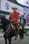 A RCMP Mountie looking debonair in his uniform as he sits upon the back of a horse at the Klondike Gold Rush National Historic Site in Dawson City in the Yukon Territories.