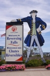 A design of a man adorned in early day clothing and a sign welcoming visitors to Reversing Falls in Saint John, New Brunswick in Canada.