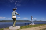 Statues of a fisherman and an Atlantic Salmon along the river bank in Campbellton, New Brunswick overlook the Restigouche River.