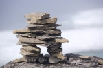 A rock sculpture or an Inukshuk atop a rock overlooking Sandy Cove along the Labrador Coastal Drive in Southern Labrador where pack ice is hidden behind the fog.