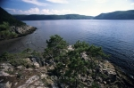 The calm waters of Sainte Marguerite Bay backdropped by the mountains in Le Parc Du Saguenay in Quebec, Canada.