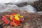 A waterfall leaves a mist behind as a colorful autumn leaf display decorates the top of one of the large boulders along the Sand River in Lake Superior Provincial Park in Ontario.