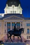 As dusk settles in around the City of Regina, Saskatachewan, the Legislative Building becomes illuminated, silhouetting the equestrian statue of Queen Elizabeth II.