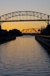 From the Soo Locks across the St. Mary's River in Sault Ste. Marie in Ontario, Canada, the sunset hues highlight the sky along with the International Bridge and train bridges.