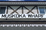 Attached to a brown and white building, the Muskoka Wharf signs is displayed in large letters for visitors to Gravenhurst, Ontario.