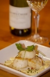 A fine presentation of seared scallops, hollandaise sauce, spices and a bottle of white wine at the Tuckamore Lodge near Main Brook, Newfoundland.