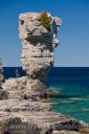 A tourist to Flowerpot Island in Fathom Five National Marine Park in Ontario, looks tiny against the sea stack resembling that of a flowerpot.