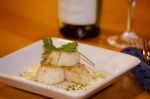 A delicious meal of seared scallops topped with hollandaise sauce and served with a glass of white wine, a gourmet meal one can expect while staying at the Tuckamore Lodge near Main Brook, Newfoundland.