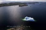 An aerial view of one single iceberg that remains in the bay along the coast of Southern Labrador near the town Charlottetown.