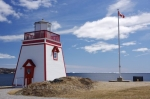 A Canada flag blows in the breeze near the rectangular red and white lighthouse building overlooking the scenery of St. Anthony Harbour in Newfoundland.
