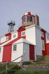 The Cape Bonavista Lighthouse along the Discovery Trail in Newfoundland, Canada is a national historic site painted in the typical red and white colors of a lighthouse except this one has two striped lines down the center.