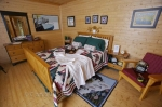 This suite at the Rifflin'Hitch Lodge in Southern Labrador, Canada is beautifully adorned with a rustic ambiance and a queen size bed.
