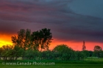 Dark cloud formations linger above the outskirts of the City of Winnipeg in Manitoba, Canada bringing on the threat of a storm, but the sunset hues change that picture very quickly.