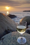Soft colors fill the sky at sunset where a glass of wine sparkles atop the rocks from the shoreline of Green Point in Newfoundland Labrador, Canada.
