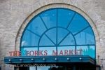 Glass which appears blue in color and red lettering marks the entrance to The Forks Market at The Forks in the City of Winnipeg, Manitoba in Canada.