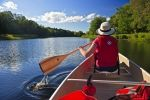 A tourist to Kejimkujik National Park in Nova Scotia, Canada, enjoys a beautiful day canoeing along the Mersey River.
