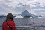 A tourist on the tour boat named the Gaffer III enjoys an Iceberg Watching Tour in Iceberg Alley in Newfoundland, Canada.