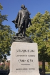 A Statue of Vauquelin stands tall in the park like setting in Place Vauquelin in Old Montreal, Quebec.