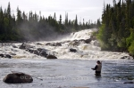 As a man stands waist deep in the White Bear River fly fishing, the massive waterfall crashes over the Southern Labrador landscape.