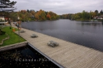The boardwalk travels along the waterfront of the Muskoka River in the town Huntsville, Ontario where people can sit and enjoy the Autumn scenery.