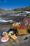 The blue sky encompasses the wilderness of the Mealy Mountains in Southern Labrador where people have taken a helicopter tour to enjoy a romantic picnic lunch.