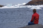 A woman sits along the shores of Quirpon, Newfoundland watching an iceberg float pass while pack ice blocks the entrance to the harbour.