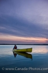 The sunset colors highlight the sky above Lake Audy in Riding Mountain National Park in Manitoba, Canada as a woman enjoys the scenery while canoeing on the calm water.