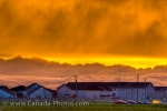 Bright yellow hues take over the sky at sunset as thick cloud formations hover over the buildings in the City of Winnipeg in Manitoba, Canada.