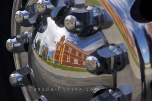 The reflections of the Parish Hall in Trinity, Newfoundland glisten in the hubs of a tour bus that is passing through town.