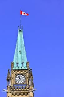 Photo of a canadian flag on top of the Government Building in Ottawa, Canada