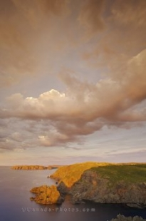 The coastal clouds hover above Notre Dame Bay in Twillingate, Newfoundland as the sun light highlights the rocky landscape.