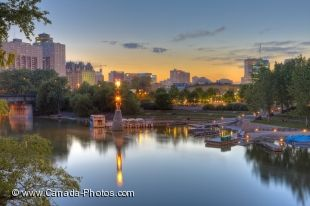 The still waters of the Assiniboine River reflect the lights of the marina and surrounding buildings at The Forks National Historic Site during dusk in the city of Winnipeg, Manitoba, Canada.