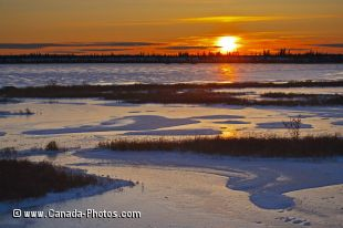 The colors from the sunset brighten the landscape across a frozen lake in the Churchill Wildlife Management Area in Churchill, Manitoba.